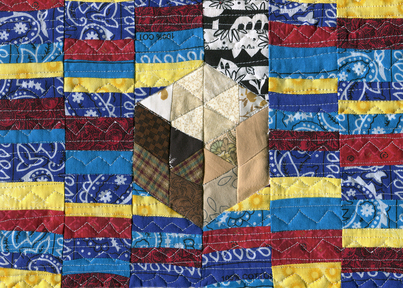 "Art accompanying the story ""Tomorrow Is Another Daze."" The piece is textile art in blue, red, and gold, with a glyph of brown and beige earth tones in the center."