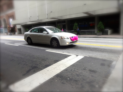 In focus image of a White vehicle on a city street with Lyft's signature pink mustache mounted to its front facing grill on an out of focus street and downtown buildings.