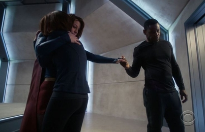 A scene from the CW's Supergirl: Kara holds her sobbing sister, Alex, with one arm while holding hands with their father-figure, J'onn, with the other as he looks down.