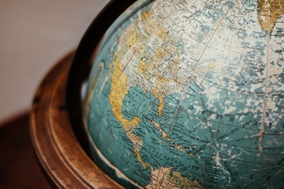 Photo is a globe in a wooden frame, taken by Adolfo Félix on Unsplash