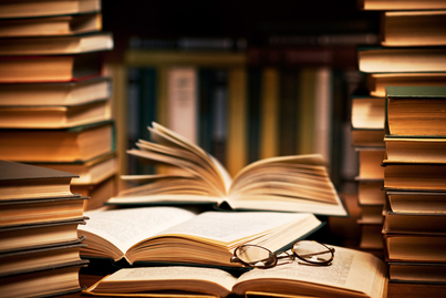 A stack of books. Three books lie open, with a pair of glasses resting on top of their open pages.