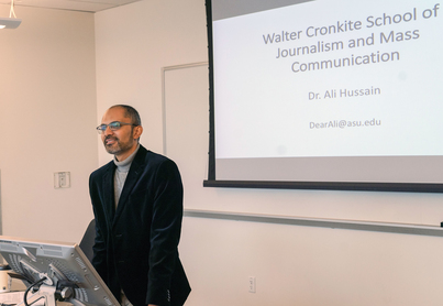 Photo Professor Hussain Presenting at a podium