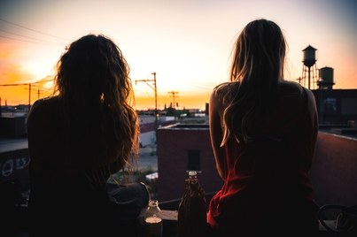 two women sit on a rooftop, with their backs to the camera and silhouetted, overlooking a cityscape with low buildings, a watertower, and either a setting or rising sun
