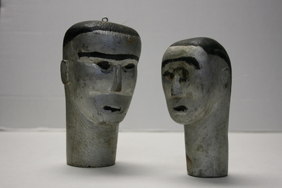 Two votive heads made out of wood and painted in silver.