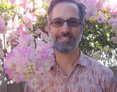 Image of Mark C. Marino in pink shirt standing near pink flowering tree