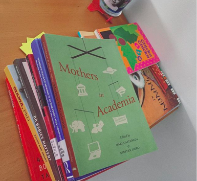 Image description: A stack of books related to academia and motherhood are juxtaposed with two children's books on a wooden dining table