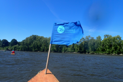 A blue flag waving on the deck of a wooden boat against a blue sky.