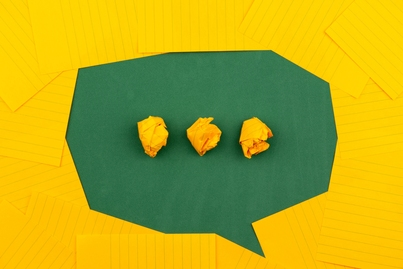 Photo of a green chat bubble with yellow background made of construction paper
