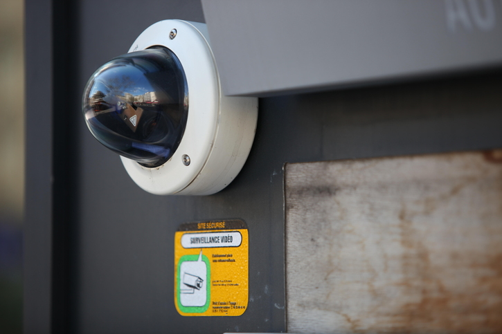 bubble dome surveillance camera mounted on the side of an exterior wall.