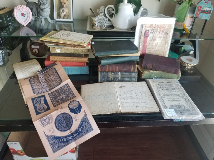 Collection of antique cookbooks stacked on a desk