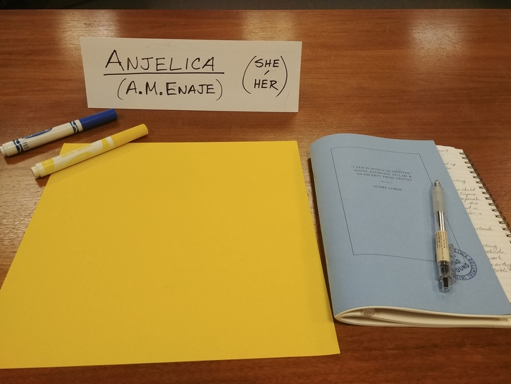 Photo of a personal desk set-up: a name card, two color markers, a sheet of yellow construction paper, a small blue booklet with a small notebook inside, and a plastic pen.
