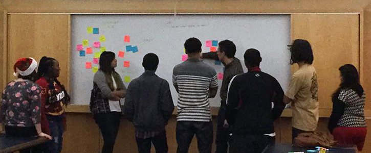 Students gather around board covered in post-in notes