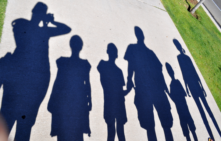 shadows of six people on ground in sun