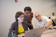 Three people discussing something on a laptop screen during a workshop.