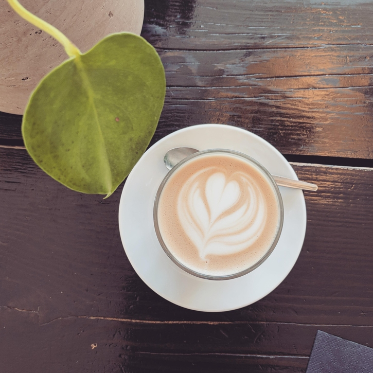 Image of latte and plant on a wooden desk