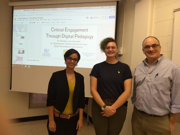"Dr. Dhanashree Thorat, An Sasala, and Brian Rosenblum standing infront of a screen which reads ""Critical Engagement Through Digital Pedagogy"""