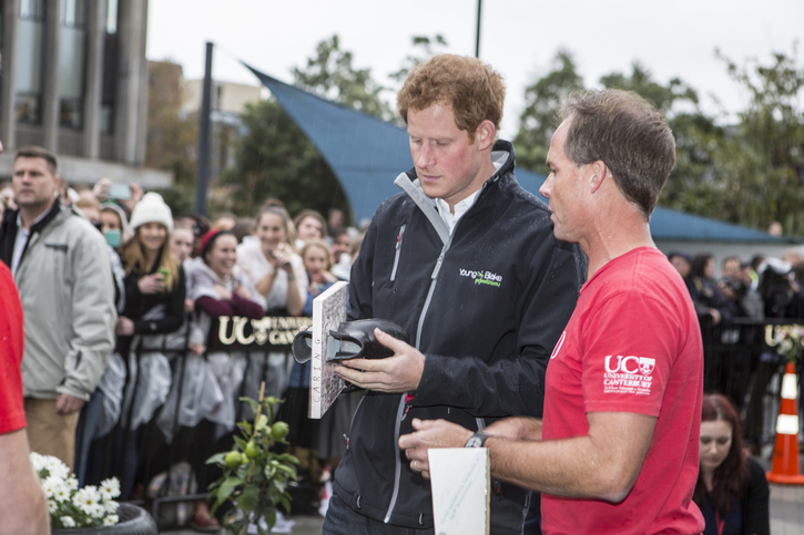 "Image description: Prince Harry stands on left holding an object that says ""caring."" Professor Osteen addresses Prince Harry about student work in a Unviersity of Canterbury shirt."