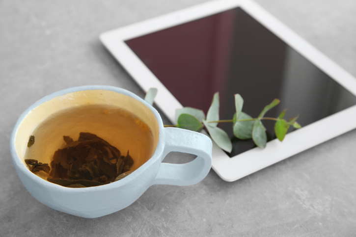A cup of tea with loose tea leaves next to a tablet