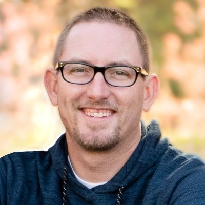 Headshot of Dr. Travis Thurston wearing a blue shirt and glasses.