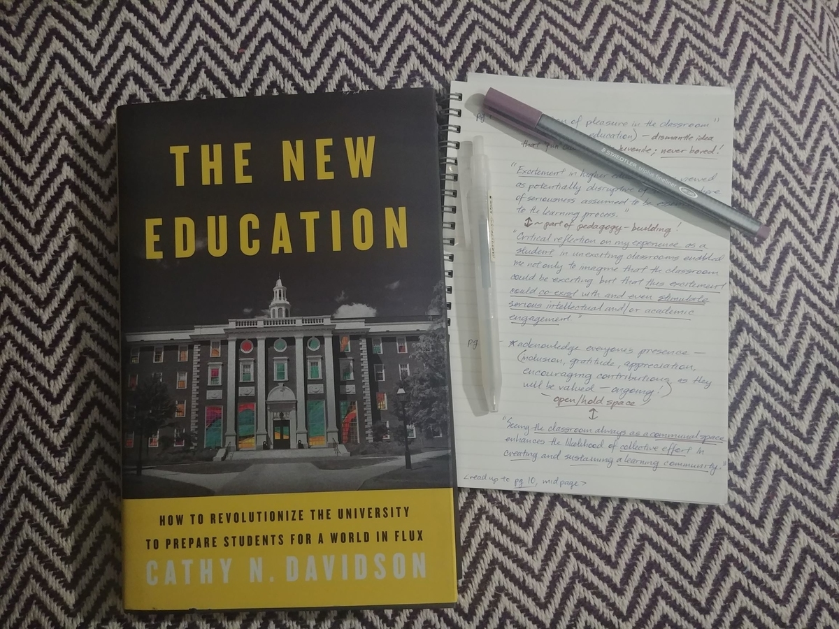 Photo of a copy of Cathy N. Davidson's book, The New Education, and a notebook containing quotes from bell hooks' book, Teaching to Transgress. Two pens scattered on notebook.