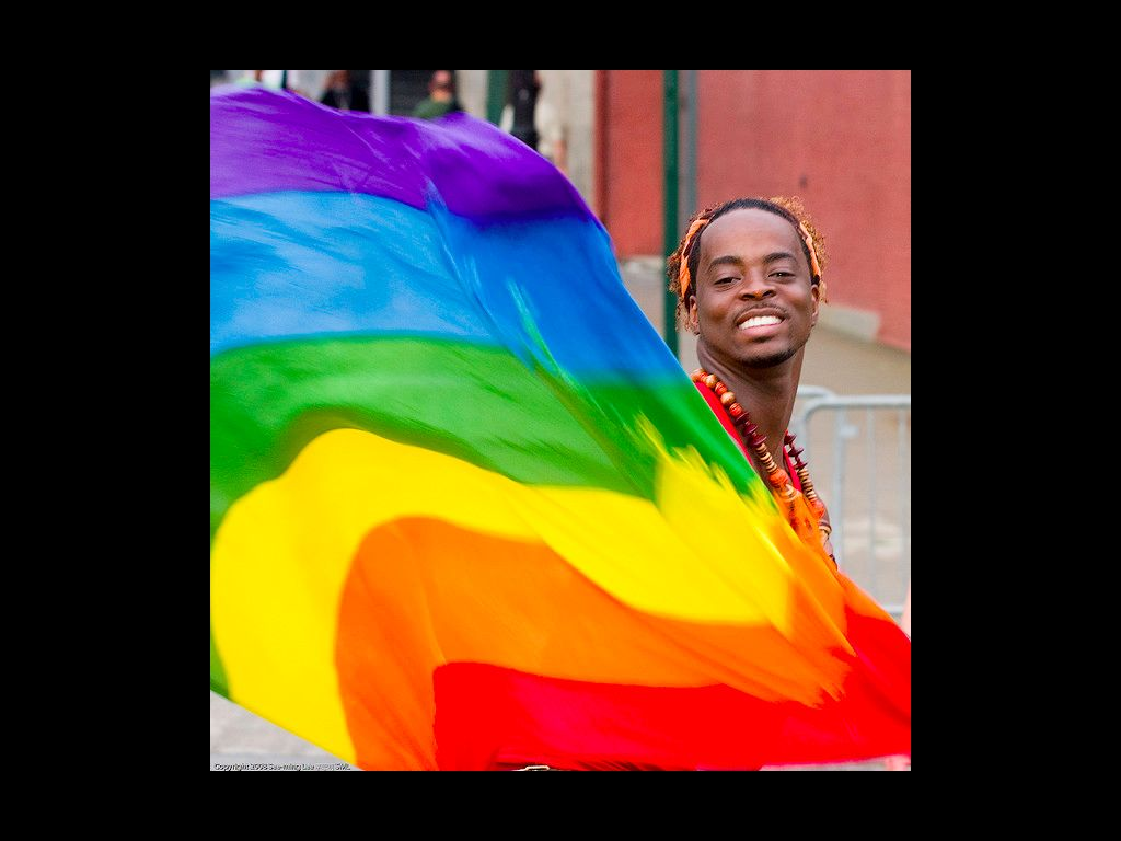 A black man with a thin mustache and close-cropped hair, wearing a red shirt with a large bead necklace in shades of red, brown, and yellow. He is smiling, and most of his body is covered by the large rainbow flag billowing in front of him.