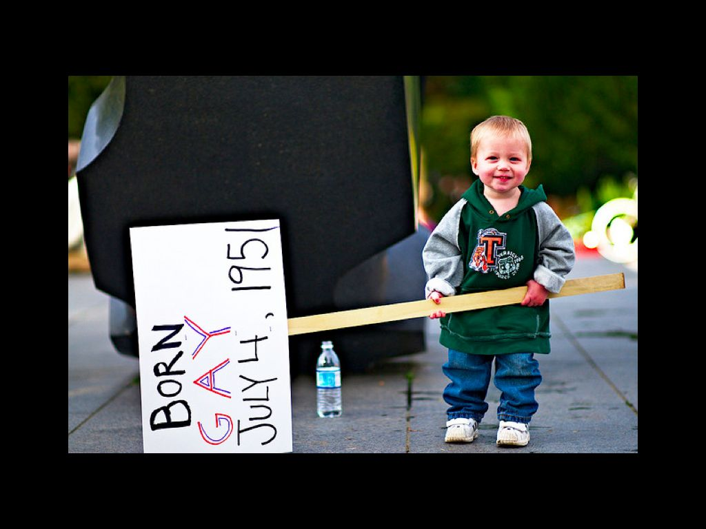 "A blonde toddler is holding a sign horizontally to his right. He is wearing a green hooded sweater with gray sleeves, jeans, and white shoes. The sign, sideways, reads ""Born GAY July 4, 1951"""
